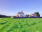 This farmhouse has farmyards and outbuildings to the rear, but faces open fields and distant sea views