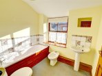 The large bathroom has a white four piece bathroom suite, with bright decor and tiling