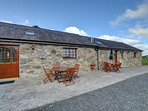 The two cottages have garden furniture on the paved area to the front