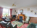 The traditional sitting room has a leather suite, easy chair, and a multi-fuel stove for cosy evenings