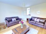 Two leather sofas provide comfortable seating in the well furnished sitting room