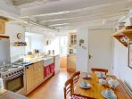 The bright kitchen has a Belfast sink and other traditional features, and includes a breakfast table and chairs for...