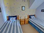 The bright and cheerful twin bedroom has a nautical theme