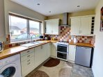 The kitchen is neatly fitted with cream units and contrasting tiled splashbacks