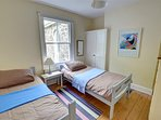 The twin bedroom is cheerful in pastel linens and light walls