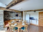 The dining area in the kitchen has a table and chairs, and bench seating built in to the interesting stone former...