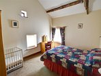 Plenty of space in the high ceilinged double bedroom for a cot if required
