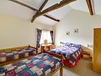 The large family bedroom, with interesting beams, has space for double and two single beds and is nicely coordinated