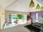 The smart, contemporary kitchen is set above the living room