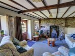 The traditional sitting room has a beamed ceiling, and a large woodburning stove in stone fireplace with original cast...