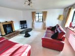 This is a spacious sitting room with electric coal effect stove, Freeview TV and DVD and large sofas