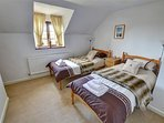 The comfortable twin bedroom has pine beds and quality soft furnishings