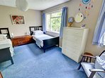 Spacious twin room, with easy chair and antique style blanket box