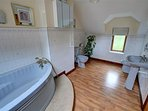 Large family bathroom on the first floor, has a corner bath, WC and bidet