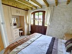 The double bedroom has a beamed ceiling and original stone wall, fitted wardrobes