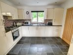 Stylish fitted kitchen including dishwasher and washing machine and slate tiled floor