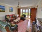 The well-furnished sitting room, with piano, has patio doors at both ends, allowing lots of light and easy access to...
