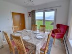 The dining area is light and bright with lovely views over the garden to the sea