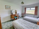The third bedroom is comfortably furnished with two single beds and has a washbasin