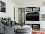 Spacious living room with air conditioning, comfy recliner, curved smart tv, sky cable tv and wifi