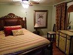 Master bedroom has leather  headboard, designer dressers