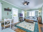 Beach inspired family room with comfortable seating, large flat screen TV, and a dining nook.