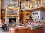 Cozy up to the wood-burning fireplace and peer at the lake through two-story tall windows