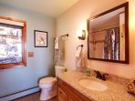 Freshen up in this pristine bathroom, offering copious amounts of counter space.