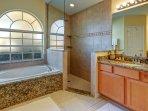 The master bathroom, with granite twin vanities, tub and walk in rain shower.