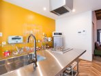 The combination of a stainless island kitchen and the orange color wall is one of the unique design