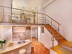Stairs lead up to the mezzanine level bedroom