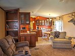 The living room flows freely into the spacious, fully equipped kitchen with a center-island chopping space, modern...
