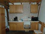 De keuken met koelkast, combimagnetron en inductiekookplaatje.