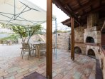 Dining area, charcoal barbecue & wood oven in the backyard under the grapevines