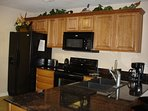 Electric range, microwave, dishwasher, refrigerator/freezer with icemaker + small appliances.