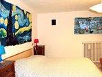 La grande camera con il letto matrimoniale e il letto singolo e attacchi d'arte sul muro.