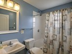 Freshen up in the charming full bathroom before resting on the cozy mattresses in the house.