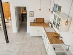 fully equipped modern kitchen seen from up the staircase.