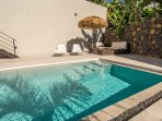 comfortable sun loungers and outdoor seating area for a relaxing pool side afternoon.