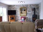 Salon avec TV et poêle à bois