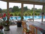 Véranda - coin repas, avec vue sur la piscine