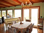 Dining table for four with french doors leading out to the ocean facing deck.