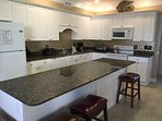Kitchen w/2 refrigerators, marble counter tops and back splash.