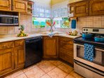 Fully equipped kitchen with fridge, microwave, stove/oven and dishwasher.