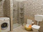 bagno con ampio box doccia e lavatrice
