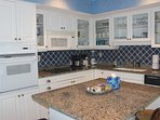 The updated kitchen features white cabinets, tile, and granite counters.