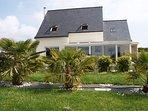 Façade de la maison avec la véranda vu de la  pelouse avec les palmiers
