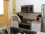 The well stocked kitchen features new stainless appliances.