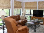 The sun room features comfortable leather furnishings and a large HDTV.