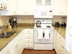 The updated kitchen has granite counter, white cabinetry, and is well stocked.